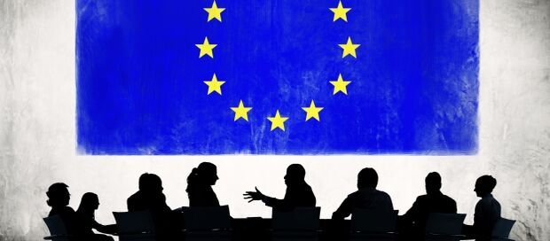 Business People Discussing with Flag of European Union Behind  c  Thinkstock
